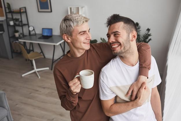 Portrait franc d'un couple gay insouciant embrassant tout en se tenant près de la fenêtre et profitant du matin ensemble à la maison, espace de copie