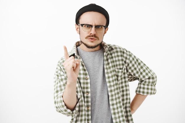 Portrait de frère sérieux et autoritaire strict avec barbe et lunettes portant bonnet noir hipster secouant l'index
