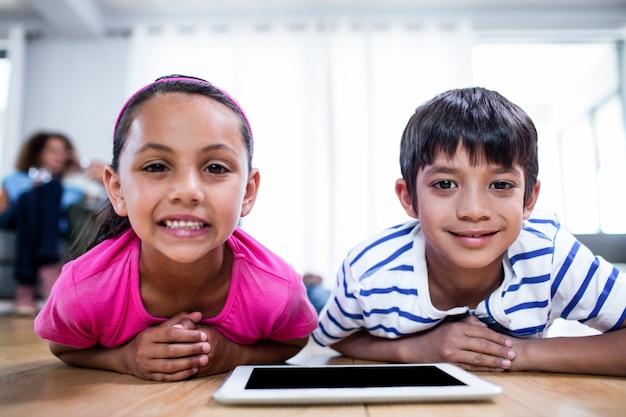 Portrait de frère et soeur allongé sur le sol avec tablette numérique
