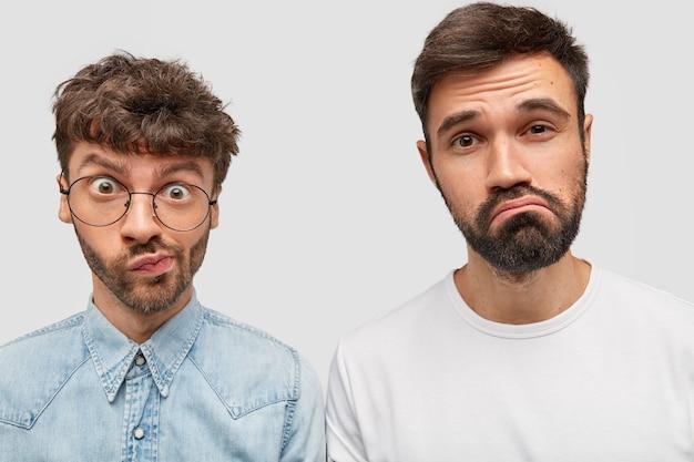 Portrait de frères barbus courbe les lèvres et ont des expressions perplexes, ressentent de l'hésitation tout en prenant une décision, reçoivent une proposition de travail à l'étranger