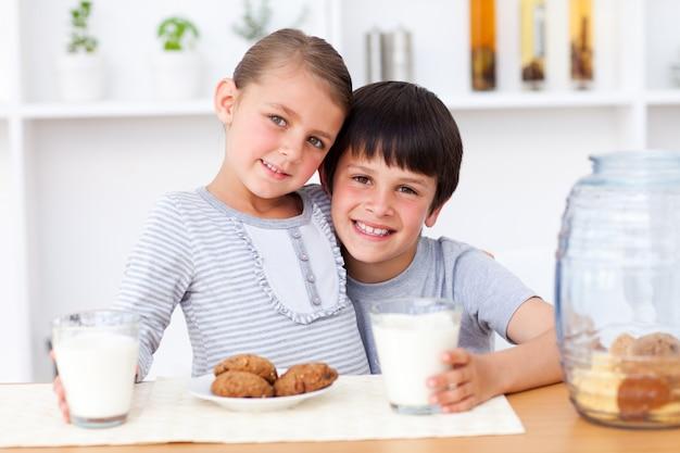 Portrait de frères et sœurs heureux manger des biscuits