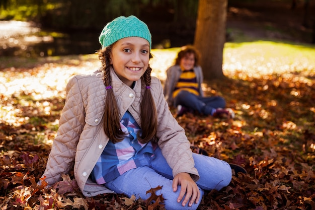 Portrait de frères et sœurs souriants assis au parc pendant l'automne