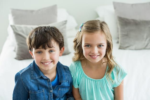 Portrait de frères et sœurs souriants assis sur un canapé dans le salon