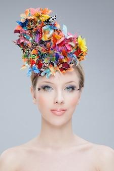 Portrait frontal d'une belle fille portant sur le dessus de sa tête un bouquet de fleurs