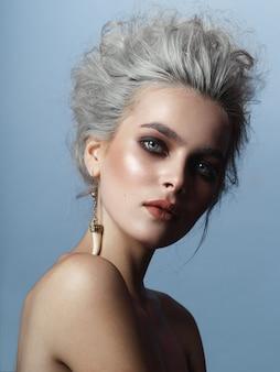 Portrait frontal d'élégante jeune femme, maquillage parfait et coiffure blonde grise, isolée sur fond bleu.