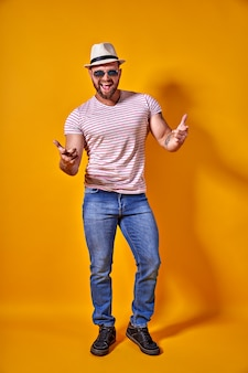 Portrait de funky guy optimiste danse porter des lunettes de soleil de chapeau de paille look été isolé sur couleur jaune ...