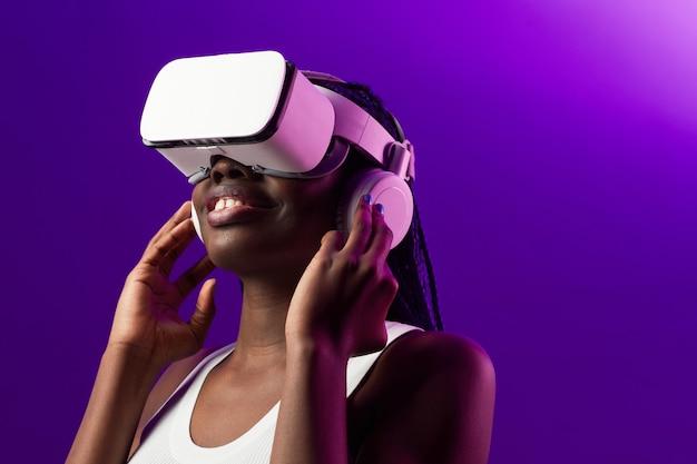 Portrait futuriste d'une jeune femme afro-américaine portant un casque vr sur fond violet, espace pour copie