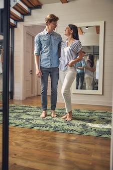 Portrait gai beau couple debout dans le salon tout en se regardant