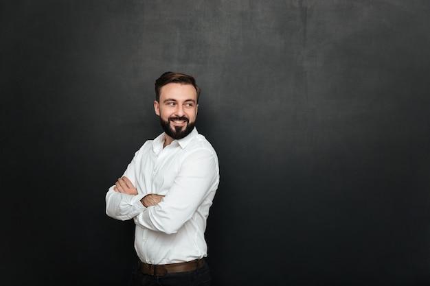 Portrait de gai homme beau debout avec les bras croisés, et en regardant en arrière sur l'espace de copie gris foncé