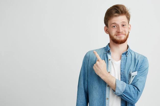 Portrait de gai jeune beau mec souriant pointant le doigt vers le haut.