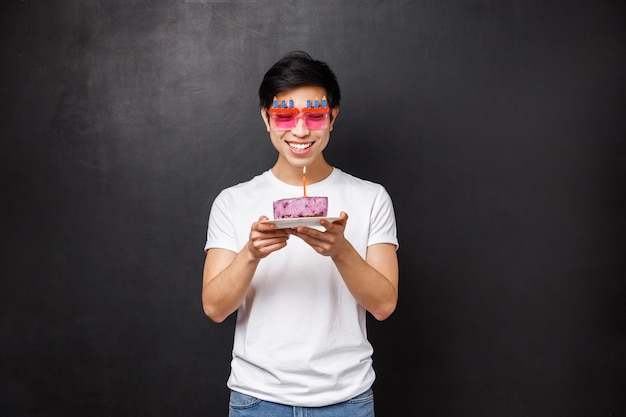 Portrait, de, gai, jeune, mâle asiatique, célébrer, b-day, souffler, bougie, sur, gâteau, et, sourire, quoique, faire, souhait