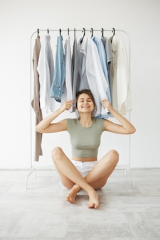 Portrait de gaie jeune femme brune souriante assise sur le sol parmi les vêtements sur la penderie sur mur blanc.