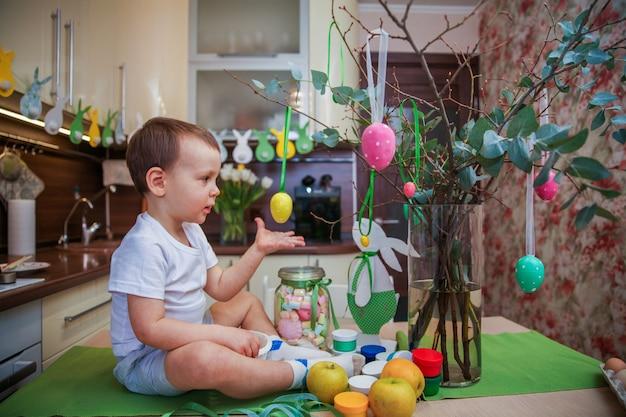 Portrait d'un garçon de 4 ans à la maison sur la table dans la cuisine décorée pour pâques