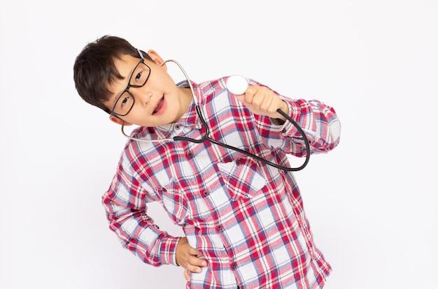Portrait d'un garçon de 8 ans faisant semblant ou jouant au docteur avec un stéthoscope.