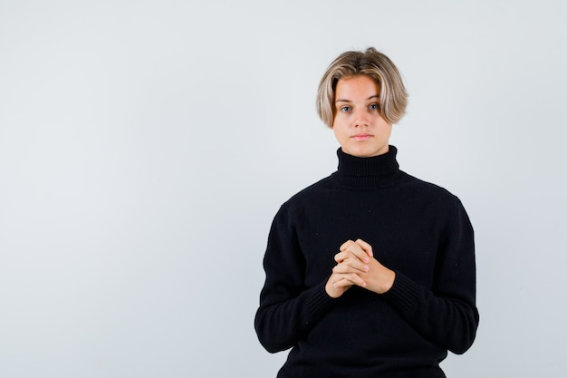 Portrait d'un garçon adolescent mignon avec les mains jointes dans un pull à col roulé noir et à la vue de face pensive