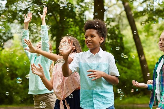 Portrait de garçon afro-américain et groupe d'enfants insouciants s'exécutant dans le parc tout en jouant avec des bulles à l'extérieur