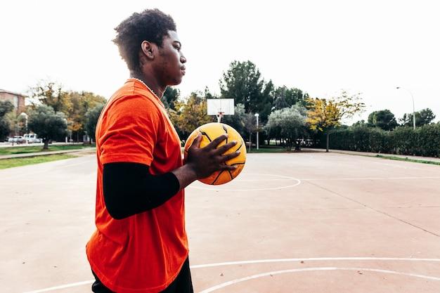 Portrait d'un garçon afro-américain noir tenant un ballon de basket contre sa poitrine sur un terrain de basket urbain. prêt à jouer.