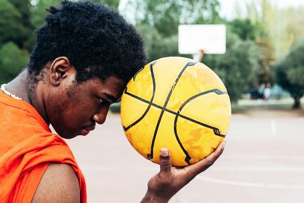 Portrait d'un garçon afro-américain noir tenant un ballon de basket dans son front sur un terrain de basket urbain. habillé d'un t-shirt orange.