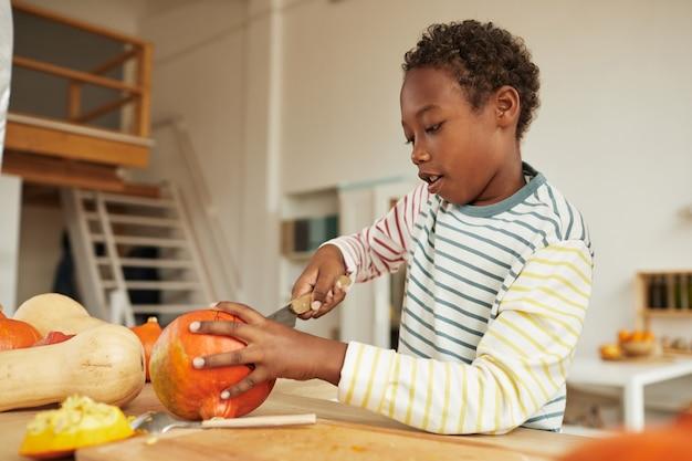 Portrait de garçon afro-américain préadolescent portant une tenue décontractée debout à table dans la cuisine de sculpture citrouille pour halloween