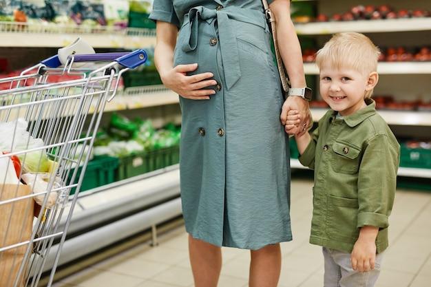 Portrait d'un garçon d'âge préscolaire heureux en chemise verte debout contre une étagère dans un magasin d'alimentation et tenant la main d'une mère enceinte