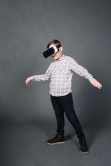 Portrait d'un garçon à l'aide de lunettes de réalité virtuelle, debout sur un fond gris