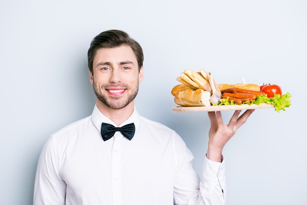 Portrait de garcon amical habillé en tenue de soirée tenant de la nourriture sur une assiette