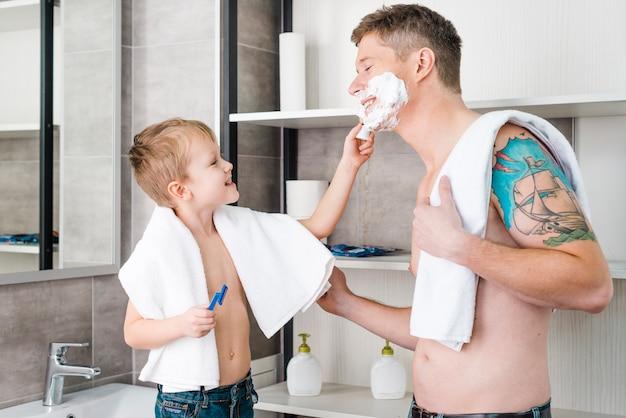 Portrait, garçon, appliquer, mousse rasage, visage, père, salle bains