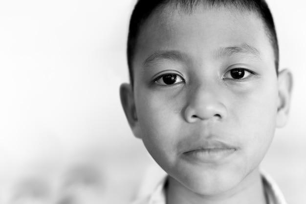 Portrait d'un garçon asiatique qui pleure avec une larme sur son visage en noir et blanc.