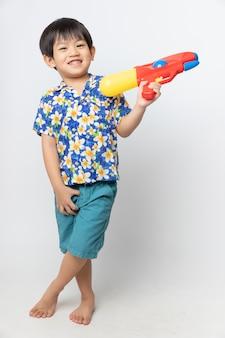 Portrait d'un garçon asiatique sourit avec un pistolet à eau