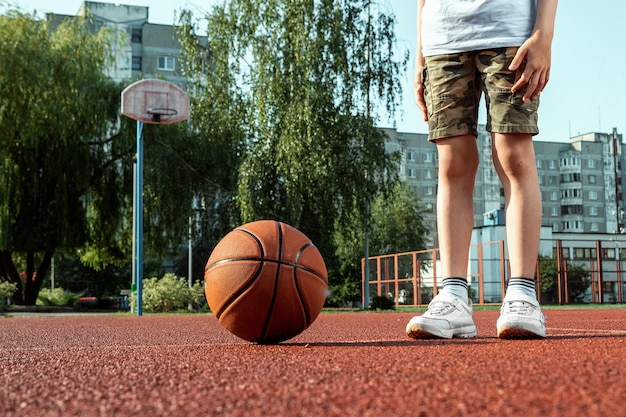 Portrait d'un garçon avec un ballon de basket sur un terrain de basket