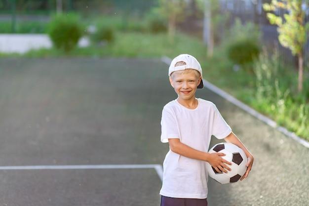 Portrait d'un garçon avec un ballon de football dans ses mains sur le terrain de football