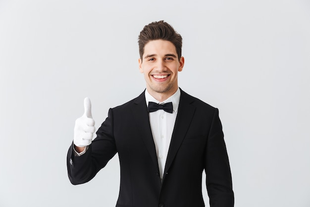 Portrait d'un garçon de beau jeune homme portant un smoking et des gants debout isolé sur un mur blanc, montrant les pouces vers le haut