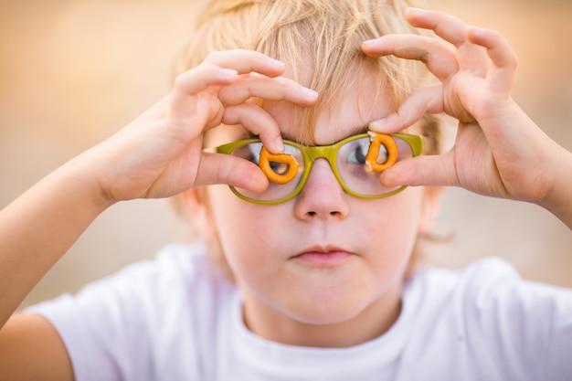 Le portrait d'un garçon blond à lunettes vertes