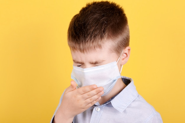 Portrait d'un garçon brune en éternuements de masque médical.
