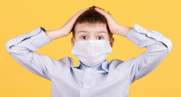 Portrait d'un garçon brune en masque médical avec les mains sur la tête, choqué, surpris.