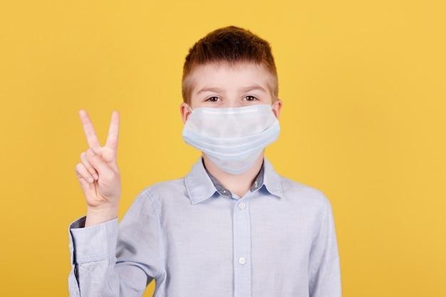 Portrait d'un garçon brune en masque médical montrant le signe de la victoire avec les doigts.