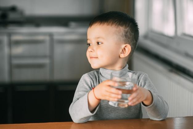 Portrait d'un garçon buvant un verre d'eau, heureux dans la cuisine très douce