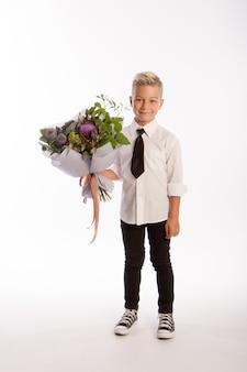 Portrait de garçon caucasien blond à la mode avec bouquet cadeau