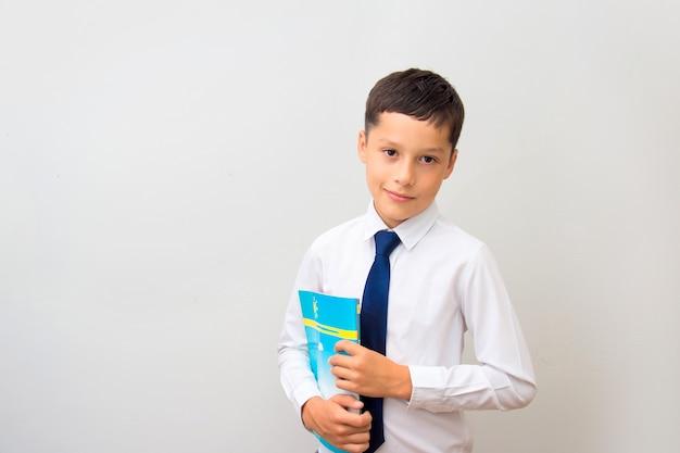 Portrait d'un garçon dans une chemise blanche et une cravate avec un livre dans ses mains