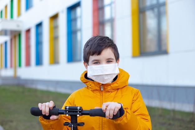 Portrait d'un garçon dans une veste jaune dans un masque médical blanc dans la rue