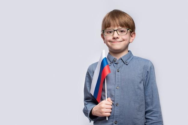 Portrait de garçon avec le drapeau de la russie en mains sur studio blanc