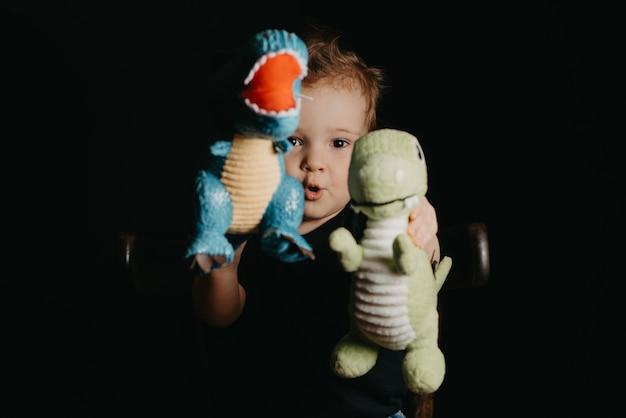 Portrait d'un garçon enfant heureux jouant avec des jouets de dinosaures
