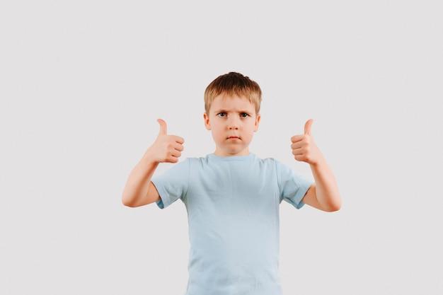 Portrait de garçon enfant sérieux donnant les pouces vers le haut de geste de la main