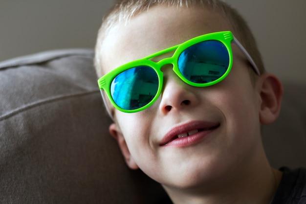 Portrait d'un garçon enfant très souriant à lunettes de soleil.