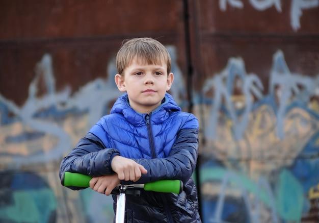 Portrait d'un garçon européen avec un scooter sur un mur avec des graffitis