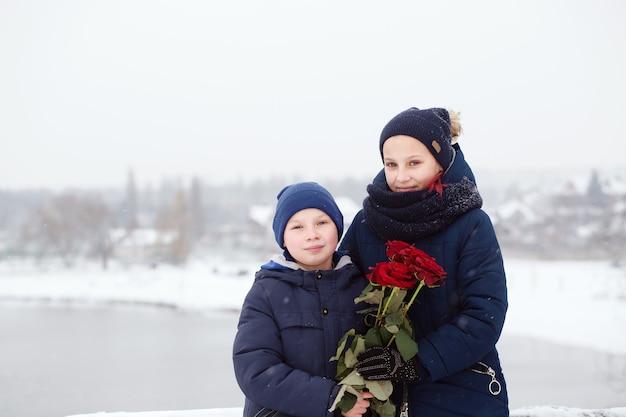 Portrait d'un garçon et d'une femme avec des roses rouges le jour de la saint-valentin