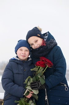 Portrait d'un garçon et d'une fille avec des roses rouges le jour de la saint-valentin