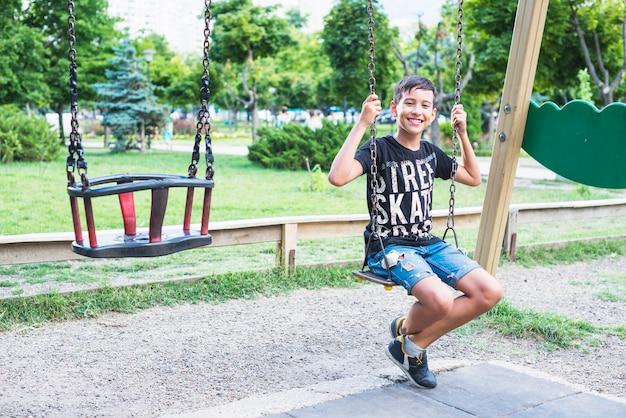 Portrait de garçon heureux assis dans la balançoire