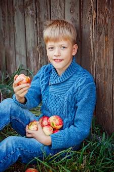 Portrait d'un garçon heureux, manger une pomme à l'extérieur à l'extérieur.