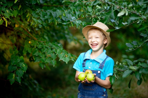 Portrait d'un garçon heureux de six ans en vêtements bleus et chapeau dans un jardin avec des pommiers